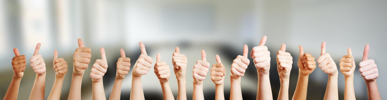 Hände mit Thumbs up Zeichen im Büro